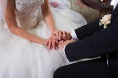 försiktiga brudgumhänder för brud Arkivbilder