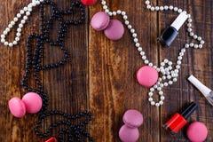 Försiktiga kexmakron på en träbakgrund med attributen av en handväska för kvinna` s fotografering för bildbyråer