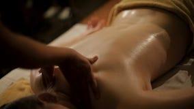 Försiktiga kvinnors händer som gör den avslappnande massagen till klienten, orientalisk terapi stock video