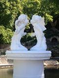 Försiktiga kyssande änglar i trädgården Ideal för hälsningkort för dagen Februari 14 för St-valentin` s Royaltyfri Foto