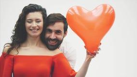 Försiktiga par skönheten av flickan och hennes stiliga grabb och att rymma hjärtan i form av ballonger och kyssar Lyckligt arkivfilmer