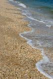 Försiktiga vågor som sveper på en kiselstensandstrand arkivbilder