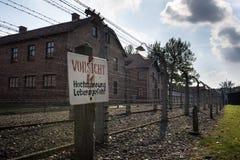 Försiktigt Hög-spänning, fara underteckna in det Auschwitz II-Birkenau lägret i Brzezinka arkivfoto