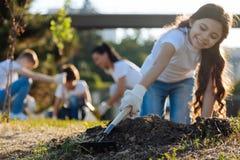 Försiktigt longhaired brunettanseende på knä, medan arbeta i trädgården arkivfoto