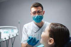 Försiktigt manligt tandläkarehållhjälpmedel i hand Han ser flickan som sitter i tand- stol i rum Hon håller munnen öppnad arkivfoton