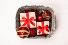 Försilvra asken med gåvor och röda julbollar på vit träbakgrund royaltyfria bilder