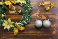 Försilvra bollar, guld- klockor, julkransuppsättning på trätextur royaltyfri bild