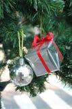 Försilvra bollen och framlägga på julträdet Royaltyfri Foto