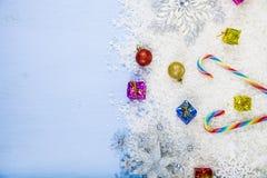Försilvra dekorativa snöflingor och snöa på en blå träbackgroun Royaltyfria Bilder