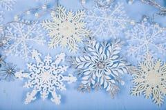 Försilvra dekorativa snöflingor på en blå träbakgrund christ Fotografering för Bildbyråer
