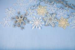 Försilvra dekorativa snöflingor på en blå träbakgrund christ Arkivfoton