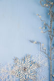 Försilvra den dekorativa snöflingor och filialen på en blå träbackgro Fotografering för Bildbyråer