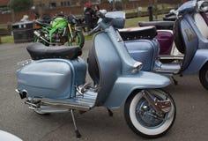 Försilvra den gråa motoriska sparkcykeln för skinande tappning som parkeras i råg Arkivfoto