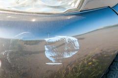 Försilvra den skadade och brutna bilen med buckliga aluminum den skrapade metallkroppen och skalningsmålarfärg från forcerad olyc Arkivbild