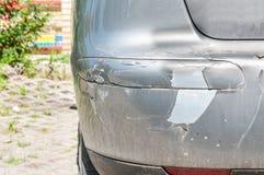 Försilvra den skadade och brutna bilen med buckliga aluminum den skrapade metallkroppen och skalningsmålarfärg från forcerad olyc Royaltyfri Fotografi