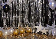Försilvra festlig bakgrund med ballonger, stjärnor och konfettier exponerade av kulöra lyktor arkivbild