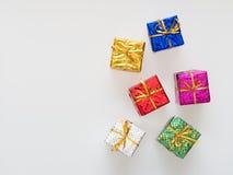 Försilvra, göra grön, slösar, rosa och guld- gåvaaskar på vit bakgrund, rött Royaltyfri Foto