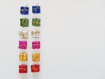 Försilvra, göra grön, slösar, rosa och guld- gåvaaskar på vit bakgrund, rött Arkivbild