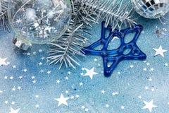 Försilvra garneringar för julträdet, glass bollar och blåa stjärnor arkivbilder
