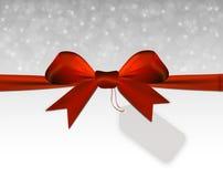 Försilvra julbakgrund med den röda pilbågen med prislappen Arkivfoton