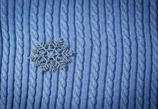 Försilvra julsnöflingan på blå stucken tygbakgrund royaltyfri foto