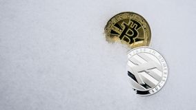 Försilvra Litecoin och den guld- bitcoincryptocurrencyen på snö Begreppet av att frilansa, börsen Guld- bitcoin på arkivbild