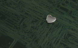 Försilvra metallisk hjärta i ett gräsplan färgat bräde för utskrivaven strömkrets Arkivbilder