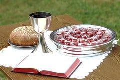 Försilvra nattvardsgångware med den öppet bibeln och bröd Arkivfoto