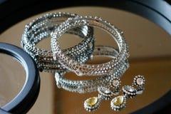 Försilvra och guld- smycken på en spegel arkivfoton