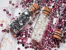 Försilvra, och rosa bergkristaller och vita pärlor i exponeringsglaskrus med trälock på marmorerar bakgrund arkivfoton