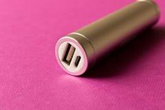 Försilvra powerbank på purpurfärgad bakgrund Begreppet av elektroniskt royaltyfri bild