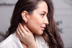 Försilvrar den härliga brunettflickan för closeupen med långt hår in smyckenörhängen, cirklar, armbandet, kedjan, halsband arkivfoto