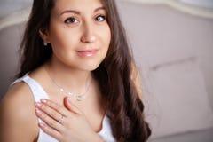 Försilvrar den härliga brunettflickan för closeupen med långt hår in smyckenörhängen, cirklar, armbandet, kedjan, halsband arkivfoton