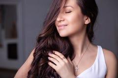 Försilvrar den härliga brunettflickan för closeupen med långt hår in smyckenörhängen, cirklar, armbandet, kedjan, halsband fotografering för bildbyråer