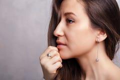 Försilvrar den härliga brunettflickan för closeupen med långt hår in smyckenörhängen, cirklar, armbandet, kedjan, halsband royaltyfri foto