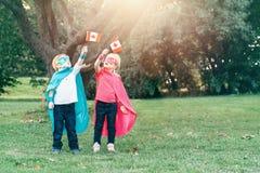 Förskole- Caucasian barn som spelar superheroes arkivfoto