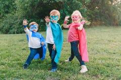 Förskole- Caucasian barn som spelar superheroes royaltyfri foto