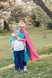 Förskole- Caucasian barn som spelar superheroes arkivfoton