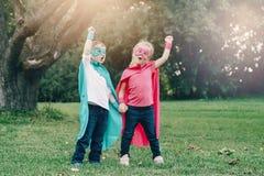 Förskole- Caucasian barn som spelar superheroes royaltyfria bilder
