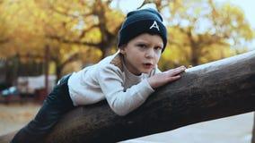 Förskole- Caucasian pojke som har gyckel på lekplats Det förvirrade nervösa barnet i hatten som klibbas på höga rep, jagar hinder stock video