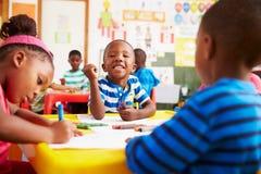 Förskole- grupp i Sydafrika, pojke som ser till kameran royaltyfri bild