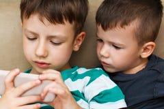 Förskole- pojkar som spelar på smartphonen fotografering för bildbyråer