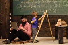 Förskole- utbildning Arithmetic kurs på skolan Lura handstil på den svart tavlan, medan den koncentrerade läraren arbetar på bärb royaltyfri bild