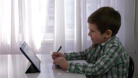 Förskole- utbildning, barnpojke använder minnestavlan för hem- undervisning och gör anmärkningar i anteckningsboken som sitter på lager videofilmer