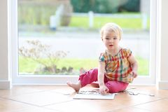 Förskolebarnflicka som spelar med pussel på golvet Royaltyfri Bild