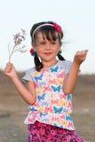 Förskolebarnflicka som utomhus poserar med den torra blomman i aftontid fotografering för bildbyråer