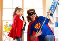 Förskolebarnflickan och hennes moder klädde som superheroes Medelålders kvinna och unge som spelar, medan göra rengöring hemma royaltyfri fotografi