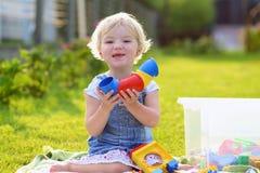 Förskolebarnflickan som spelar med plast-, blockerar utomhus Royaltyfri Bild