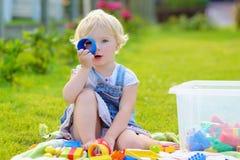 Förskolebarnflickan som spelar med plast-, blockerar utomhus Arkivfoto