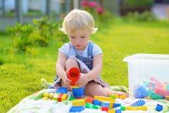 Förskolebarnflickan som spelar med plast-, blockerar utomhus Fotografering för Bildbyråer
